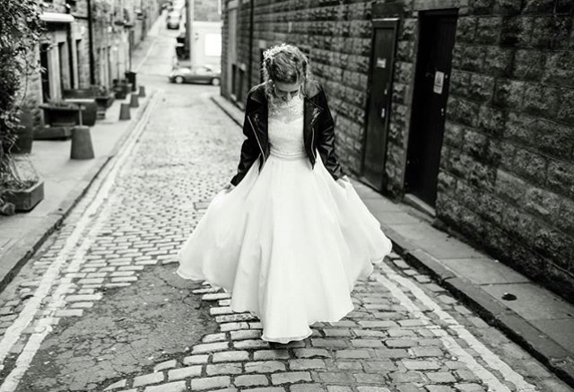 Bride wears black leather born to thread jacket on her wedding day